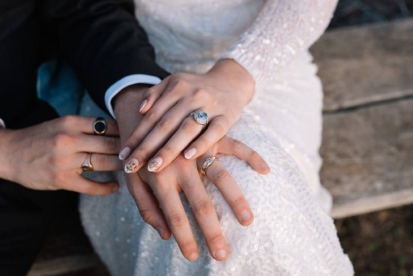 a bride and groom hands on laps with rings